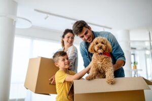 Happy family with children moving with boxes in a new apartment house